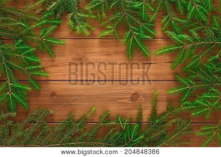 Christmas background with copy space, top view on pine tree twigs frame on natural rustic wood table surface. Xmas decorations, winter holidays concept