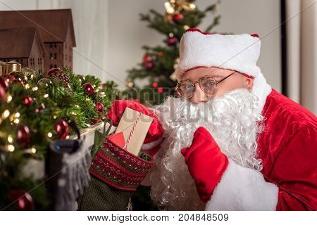 Portrait of mysterious Santa Claus gesturing secretly while hiding gift box in big decorative sock. He is looking at camera with joy