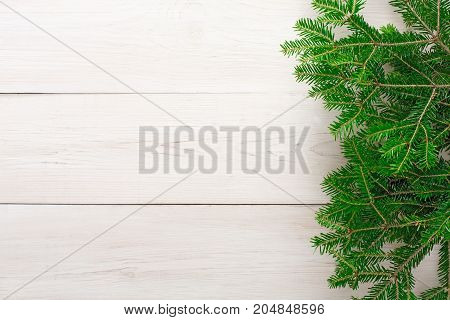 Fir tree twigs border background. Top view on christmas decoration on white rustic wooden table, copy space. Xmas and winter holidays concept