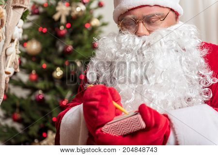 Portrait of kind old bearded man making notes on present box with concentration. He is standing in Christmas costume with fir-tree on background
