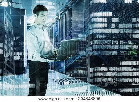 young engineer in the room data center with a laptop in hand on the background of night skyscrapers. The concept of big data in business