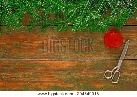 Christmas DIY background. Scissors and satin ribbon on rustic wood with fir tree branches border. Handmade hobby and winter holidays concept, top view, copy space.