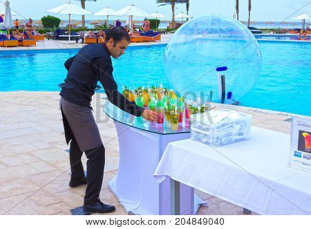 Sharm el Sheikh -April 12, 2017: The hotel worker preparing cocktails in a swimming pool at Sharm el Sheikh on April 12, 2017