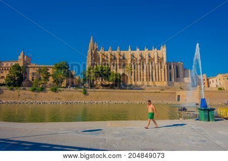PALMA DE MALLORCA, SPAIN - AUGUST 18 2017: Unidentified people walking throught the city with a Cathedral of Santa Maria of Palma La Seu in the horizint in a gorgeous blue sky, in Palma de Mallorca, Spain.