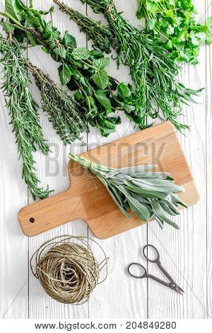 making spices with fresh herbs and greenery for cooking on white wooden kitchen table background top view