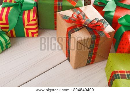 Creative presents border background. Colorful gift boxes for any holiday decorated with ribbon bows on white wood with copy space.