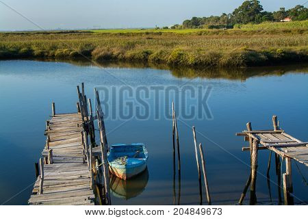 old fishing boat doked in calm water in comporta alentejo Portugal.