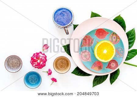 Tableware pattern. Cups and plates decorated by exotic leaves and fruits on white background top view.
