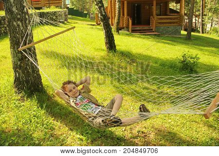 happy cheerful child smiling and lying resting in a hammock in the woods in a glade in summer among the bright green grass