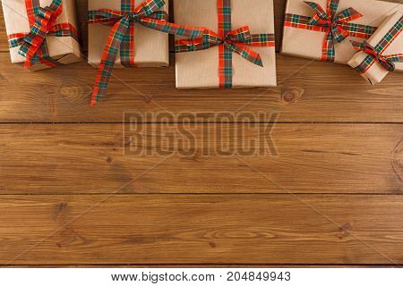 Gift boxes border, top view with copy space on wood table background. Frame of colored packages with red, green ribbons for christmas, valentine day or birthday