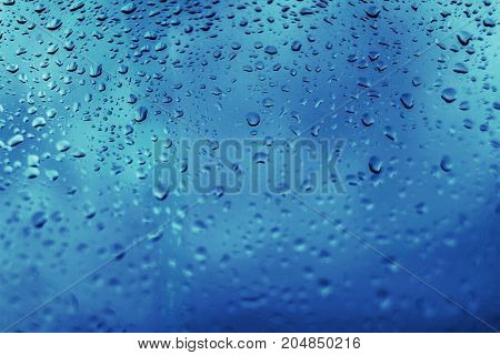 Drops of rain on blue glass background. Natural Pattern of raindrops. Rain in the city