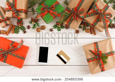 Preparing for holidays background. Gift boxes border, mobile and credit card on white wood. Seasonal sales, online sopping, presents for any holiday concept. Top view, flat lay, copy space