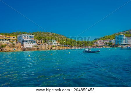 SANT ELM, MAJORCA, SPAIN - AUGUST 18 2017: Unidentified people swimming in the ocean at Sant Elm, in a beautiful blue water and sky in Majorca, Spain.
