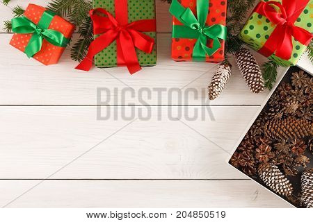 Gifts in colorful wrapping paper decorated with satin ribbon bows border and box full of pine tree cones on wooden background. Presents for christmas, valentine day or birthday, top view, copy space