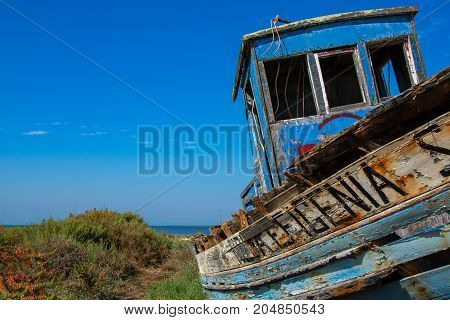 abandoned old fishing boat lying near the water in comporta alentejo Portugal.