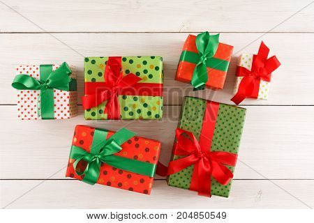 Gift boxes in colorful dotted paper decorated with satin ribbon bows on white wooden background. Presents for christmas, valentine day or birthday, top view, copy space