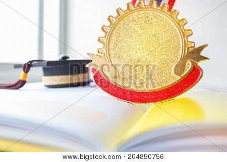 Golden medals and Graduation cap on book graduate education in university Competitions and Education study concepts. Success in study famous institution Concept of winner abroad international