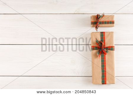 Top view on gift boxes in craft wrapping paper tied with checkered satin ribbon on white rustic table with copy space. Christmas, birthday or valentine day present concept
