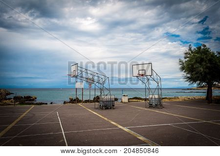Basketball playground by the sea in a cloudy day of autumn - Porto Tores - Sardinia
