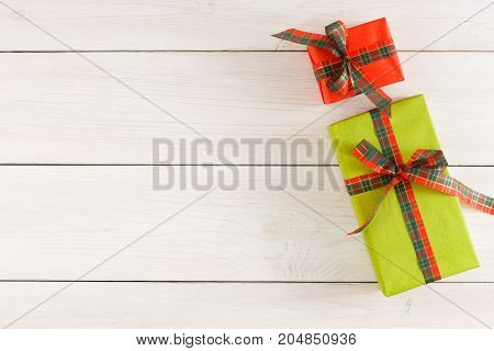 Top view on gift boxes in colorful dotted wrapping paper tied with checkered satin ribbon on white rustic table with copy space. Christmas, birthday or valentine day present concept