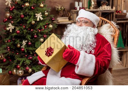Merry Christmas. Portrait of joyful Father Frost holding box present box while sitting on comfortable armchair. He is looking at camera and smiling