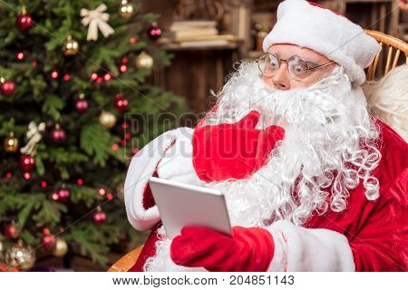 Portrait of Santa Claus looking at tablet with shock. He is sitting in red and white costume near Christmas tree