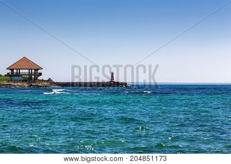 wooden house Bungalow and a lighthouse on the seashore