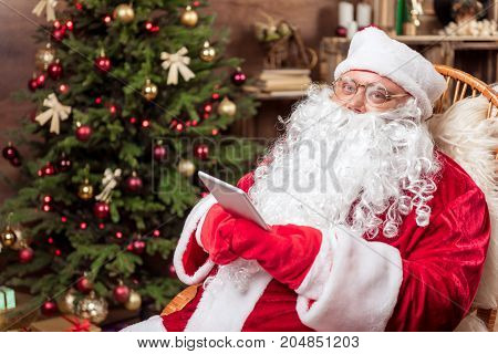 Portrait of happy old Santa using modern digital gadget while relaxing on his armchair hear fir-tree. He is looking at camera with kindness