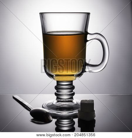 A beautiful transparent glass with a dark hot drink. Sugar and a spoon are lying on the table. Unusual advertising still life. Morning tea. White background.