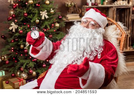 Soon will be midnight. Portrait of cheerful Santa Claus holding clock and looking at camera with excitement. He is relaxing on armchair near fir-tree