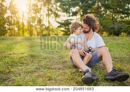 Father son hugging playing on the grass in the park. Father's Day.