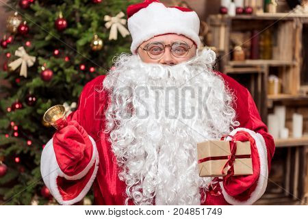 Happy New Year. Portrait of joyful Santa ringing the jingle bell and holding gift box. He is standing near Christmas tree
