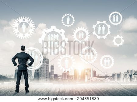 Back view of businessman looking at modern cityscape and gear connection idea