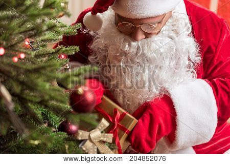 Careful mysterious grandfather in red and white costume hiding present under Christmas tree