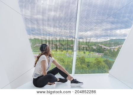 Young attractive woman dressed in casual clothing sits on a white floor from a modern building and looks through a very tall window.