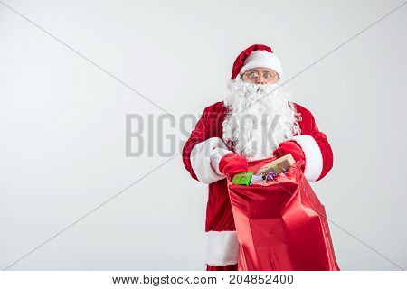 I have lots to do. Portrait of senior Santa Claus holding big sack with many presents. He is standing and looking at camera with shock. Isolated and copy space