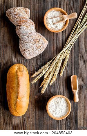 baking fresh wheaten bread on bakery work table wooden background top view