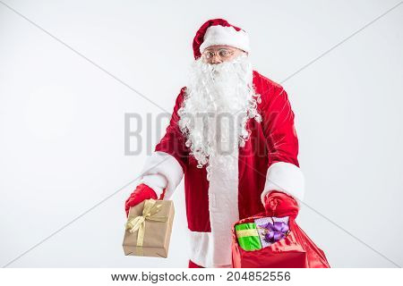 Portrait of kind old Father Frost carrying many presents in red sack. He is standing and looking at camera with surprise. Isolated and copy space