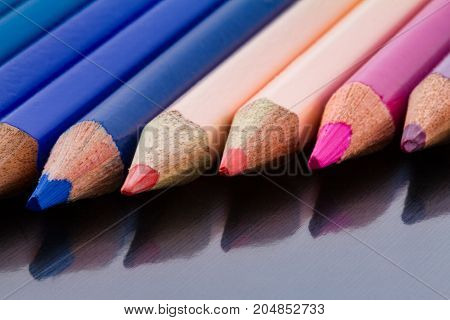 Color Pencils In Diagonal Formation And Underlying Surface Reflection Close-up