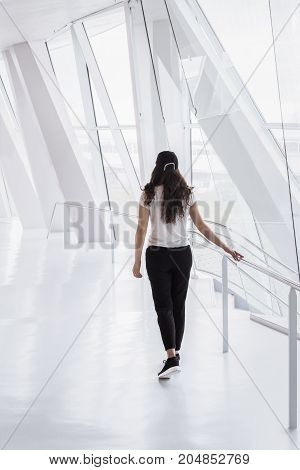 Young woman dressed casual walks on a bright white hallway from an office building with tall windows and modern columns.