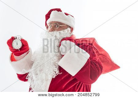 Soon will be New Year. Waist up portrait of cheerful Father Frost waiting for midnight. He is carrying red sack on shoulder and looking at camera with seriousness. Isolated