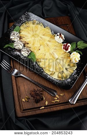 Carpaccio of pineapple with sauces on a dark background.