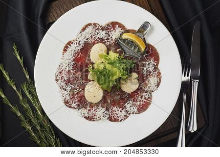 Carpaccio with lettuce leaves on a dark background.