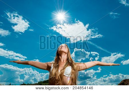 Beautiful Woman With Arms Outstretched Against The Background Of The Sun And Sky In A Bikini