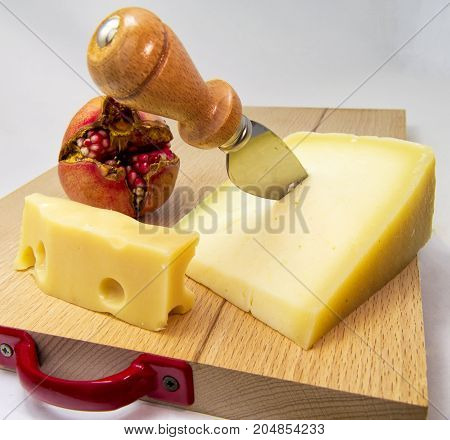 wood chopping board with assortment of cheeses and pomegranate fruit. for food concept
