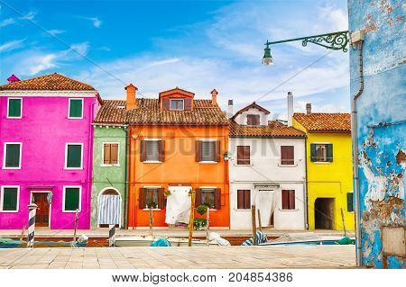 Colorful houses in Burano island with cloudy blue sky near Venice, Italy. Popular and famous tourist place.