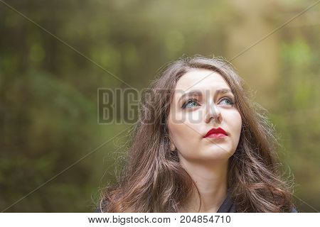 Beautiful caucasian woman with green eyes and red lips looking to her left towards the beam of light.