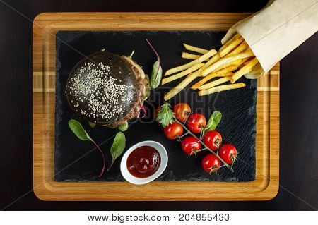 Black double hamburger made from beef with jalapeno pepper, cheese and vegetables. Nearby is French fries and cherry tomatoes. View from above.