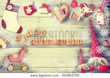 Christmas Greeting Card with Xmas Elements wooden cubes and Toys on Gray Wooden Background with Snow Frame. Retro Style. Vintage Toned.