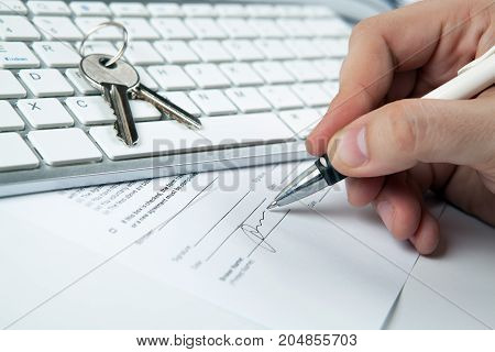 apartment keys mortgage loan document and a keyboard and a human hand
